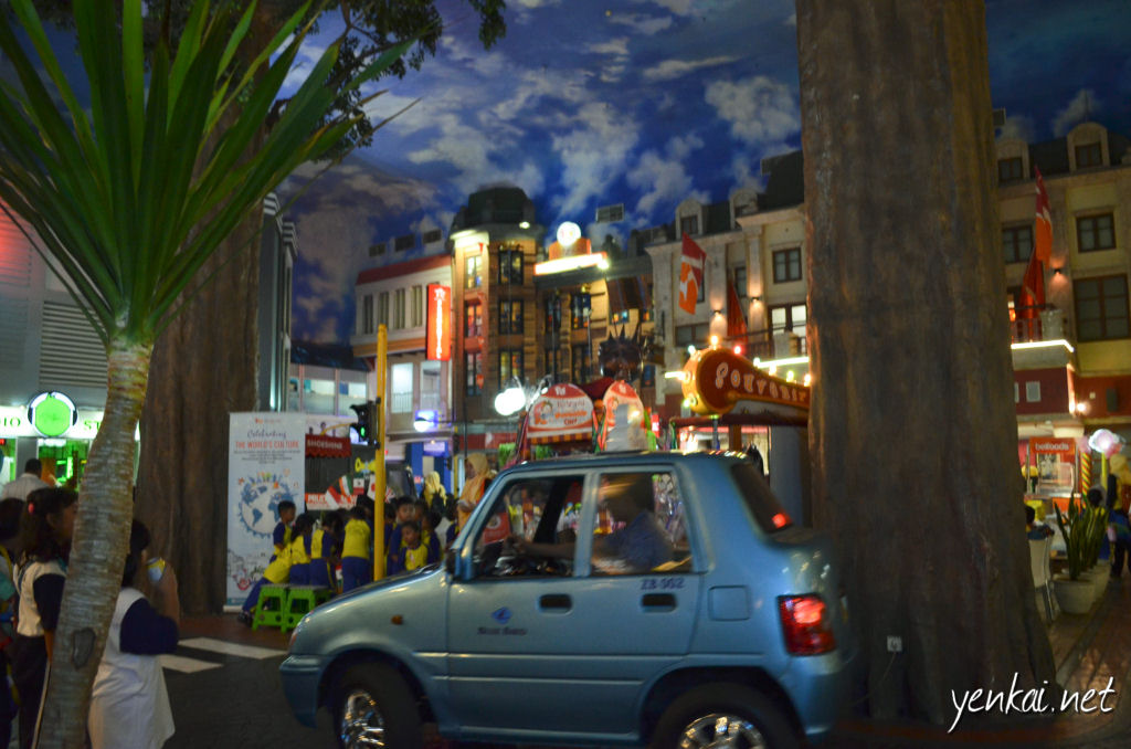 A Blue Bird taxi making its way around the town square