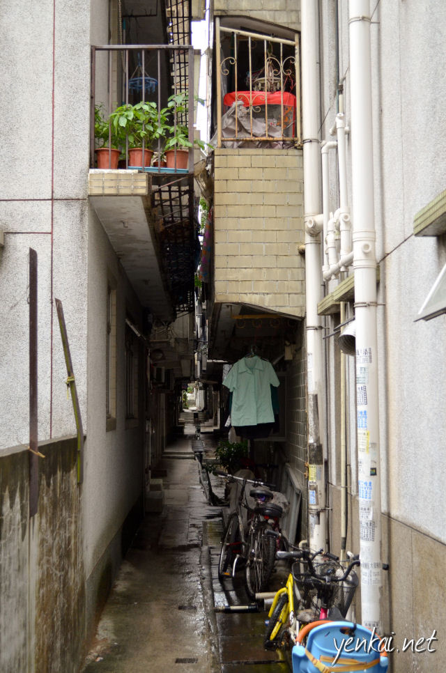 Makes me wonder what is the point of having a balcony. I guess it maximizes the space that can be utilized. The alley separating the buildings is compulsory, but the building owners are free to extend the building with balconies over the alley.